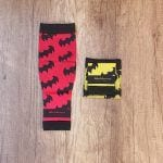 Medias compresivas desplegadas rojas con logo de batman en negro, al lado media compresiva doblaba amarilla con logo de batman en negro