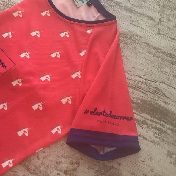 Camiseta manga corta con unicornios repetidos con detalles en azul marino, se visualiza la manga izquierda y parte de la parte delantera de la camiseta de #elartedecorrer Barcelona