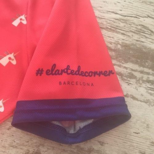 Camiseta manga corta con unicornios repetidos con detalles en azul marino, se visualiza la manga izquierda de la camiseta de #elartedecorrer Barcelona