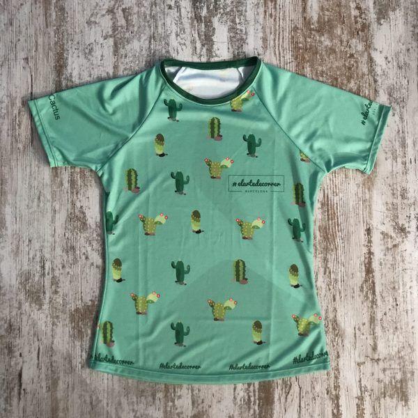 Camiseta con el logo de #elartedecorrer donde se ven diferentes tipos de cactus. Fondo de color verde.
