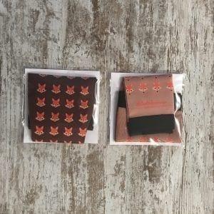 Imagen de las dos versiones de las medias compresivas de #elartedecorrer colección zorro. Marrón oscuro y marrón claros con zorros en naranja.