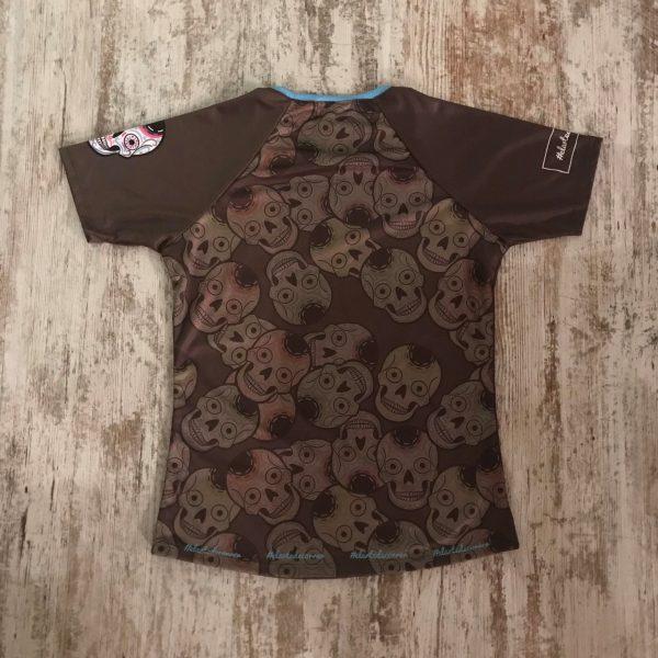 Camiseta de mujer de calaveras mexicanas con teextura repetida de diferentes calaveras por detrás de #elartedecorrer