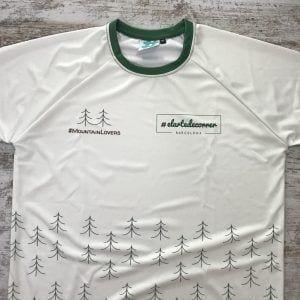 Camiseta técnica unisex Mountain Lovers, aparece expuesta sobre madera. Motivo pinos que definen una nueva colección para hombres y mujeres, amantes de la montaña.