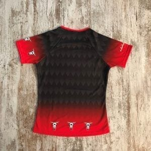 Camiseta del grupo Liquen parte posterior . Se ve el degradado y la cabeza de vaca en el pecho, en negro y rojo. Modelo de mujer.