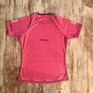 """Camiseta técnica mujer rosa y lila con las racholas de barcelona en gris encima. Se lee la frase en catalán """"Que sóc de Barcelona...i moro de calor"""", y en castellano pone, """"Dejé mi huella en Barcelona. Y Barcelona me la dejó a mi"""". Parte posterior donde indica #Barcelona."""