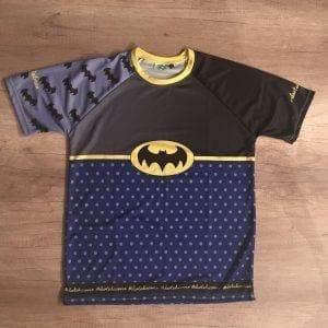 Camiseta original de Batman para correr. En la imagen se ve la camiseta de frente: una manga con logos de batman y otra lisa. En el pecho un gris a negro degradado con el logo en grande en amarillo y negro en el pecho. Debajo, un azul con topos que hace de esta camiseta especial y única.