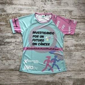 """Camiseta Corre Con Fero edición 2019, tonos lilas, verde con la frase """"Investigando por un futuro sin cáncer"""""""