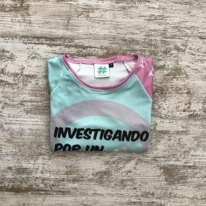 """Camiseta Corre Con Fero edición 2019, tonos lilas, verde con la frase """"Investigando por un futuro sin cáncer""""-doblada"""