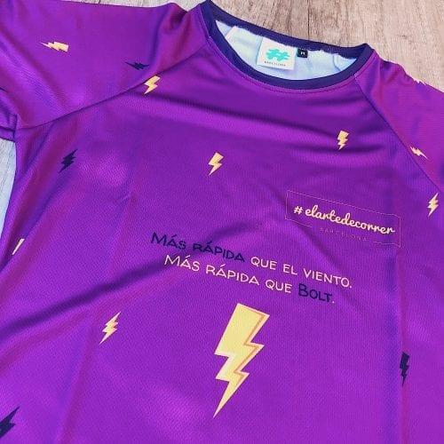 """Camiseta Manga Larga mujer Rayo por delante, fondo lila y rayos color azul y amarillo. Detalle de la frase """"Más rápida que el viento, más rápida que Bolt"""". Complementos de rayo."""