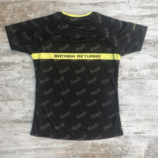 """Camiseta de mujer batman negra con logos por toda la camiseta y el foco de batman por detrás con la frase """"batman returns"""""""