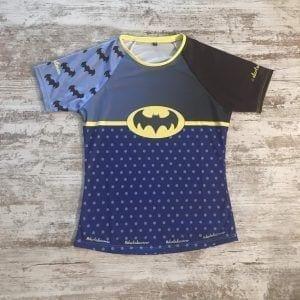 Camiseta original de Batman para correr. En la imagen se ve la camiseta de frente: una manga con logos de batman y otra lisa. En el pecho un gris a negro degradado con el logo en grande en amarillo y negro en el pecho. Debajo, un azul con topos que hace de esta camiseta especial y única. Modelo de mujer.