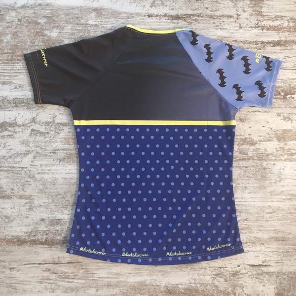 Camiseta original de Batman para correr. En la imagen se ve la camiseta de frente: una manga con logos de batman y otra lisa. Debajo, un azul con topos que hace de esta camiseta especial y única. Modelo de mujer, parte posterior.