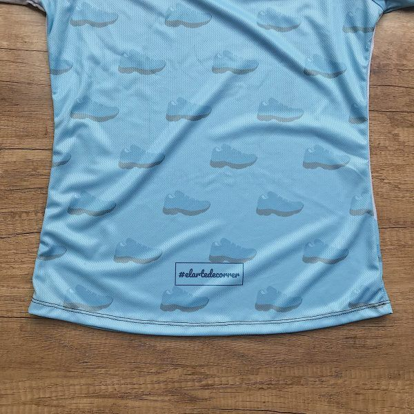 Camiseta técnica Estado Civil Runner, color azul. Se casan un para de zapatillas de running, parte de detrás lleno de zapatillas con detalle.