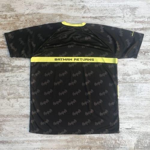 """Camiseta unisex batman negra con logos por toda la camiseta y el foco de batman por detrás con la frase """"batman returns"""""""