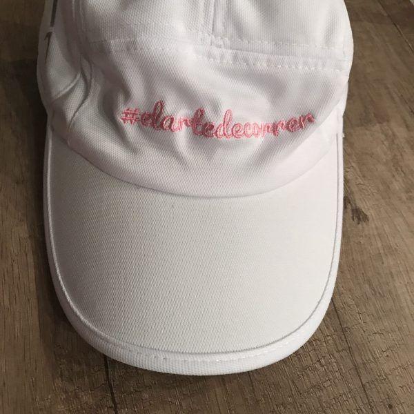 Gorra técnica blanca con logo de #elartedecorrer bordado en rosa de cerca