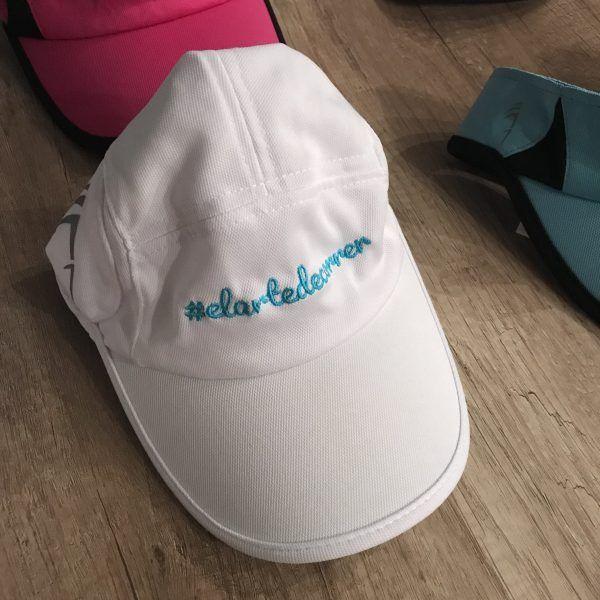 Gorra técnica blanca con logo de #elartedecorrer bordado en turquesa