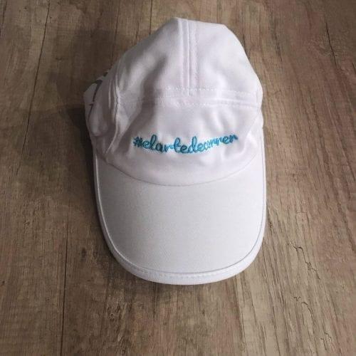 Gorra técnica blanca con logo de #elartedecorrer bordado en turquesa centrado