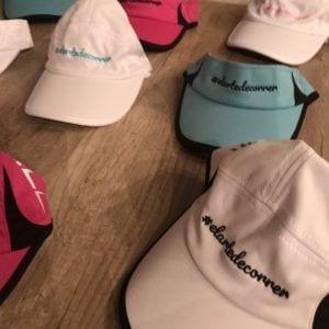 Gorras técnicas blanca y blanca-negra con logo de #elartedecorrer bordado en turquesa y negro