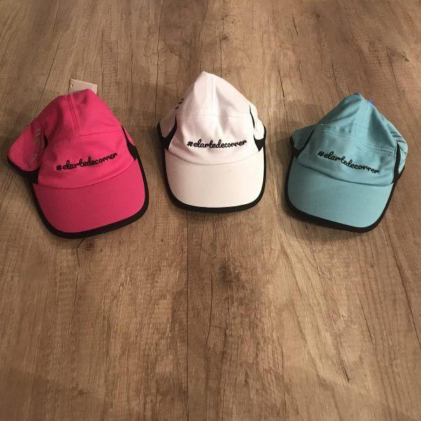 Gorras técnicas en blanco, rosa y azul cielo con logo de #elartedecorrer bordado en negro