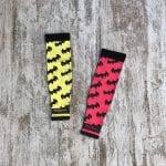 Manguito color rojo con logos de batman y manguito amarillo con logos de batman en negro.