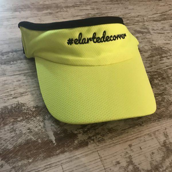 Visera amarilla con logo negro y cinta de #elartedecorrer