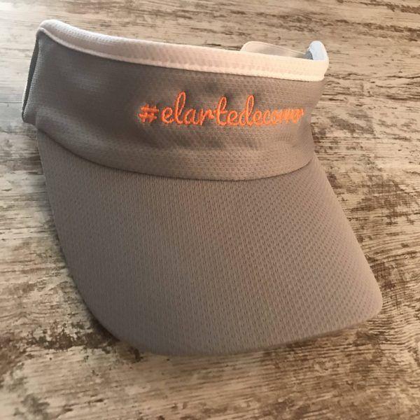 Visera gris con logo naranja y cinta de #elartedecorrer